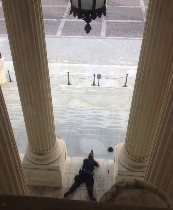 A law enforcement officer takes station near the entrance of the U.S. Capitol after reports of shots fired.