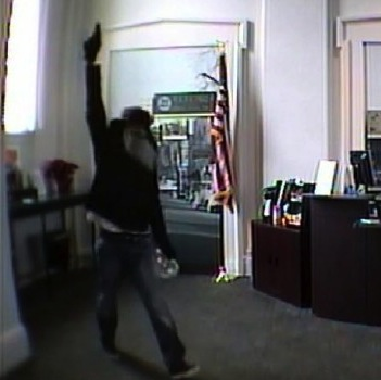 Security camera footage captures a man wearing a Santa-style beard as he fires shots and robs a PNC bank in Laurel on Dec. 21. (Laurel Police)